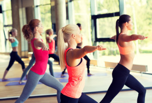 group of smiling women practising yoga in gym